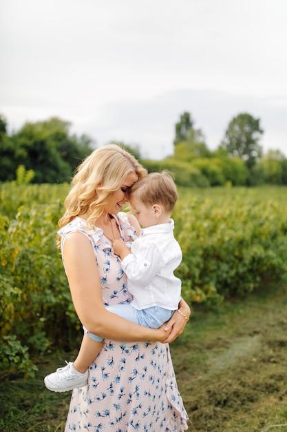 Szczęśliwa Blond Kobieta I ładny Mały Chłopiec Stojący W Letnim Ogrodzie Darmowe Zdjęcia