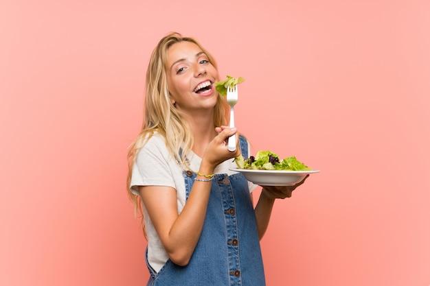 Szczęśliwa blondynki młoda kobieta z sałatką nad odosobnioną menchii ścianą Premium Zdjęcia