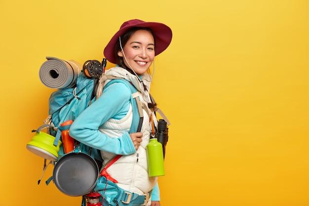 Szczęśliwa Brunetka Azjatycka Podróżniczka Nosi Duży Plecak Turystyczny, Używa Lornetki W Podróży, Stoi Przy żółtej ścianie, Nosi Stylowy Kapelusz, Sweter Z Kamizelką Darmowe Zdjęcia