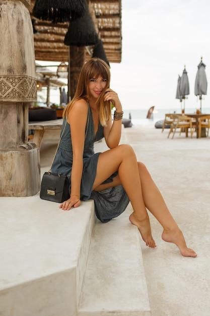 Szczęśliwa Brunetka Kobieta W Sexy Sukienka Pozowanie W Stylowej Restauracji Na Plaży W Stylu Balijskim. Pełna Długość. Darmowe Zdjęcia