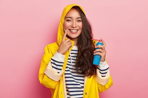 Szczęśliwa Brunetka Leczy Ból Gardła Sprayem, Ubrana W żółty Płaszcz Przeciwdeszczowy Z Kapturem, Chora Po Długim Spędzaniu Czasu Na świeżym Powietrzu W Deszczowy Dzień Darmowe Zdjęcia