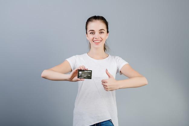 Szczęśliwa brunetki kobieta z kredytową kartą w ręce pokazuje aprobaty odizolowywać nad popielatym Premium Zdjęcia