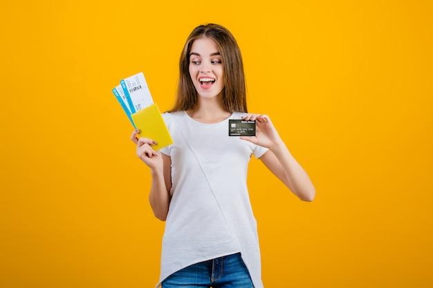 Szczęśliwa brunetki kobieta z płaskimi biletami w paszporcie i kredytowej karcie odizolowywających nad kolorem żółtym Premium Zdjęcia