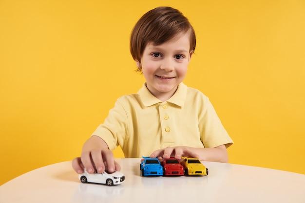 Szczęśliwa Chłopiec Bawić Się Z Wzorcowymi Samochodami Na Stole. Premium Zdjęcia