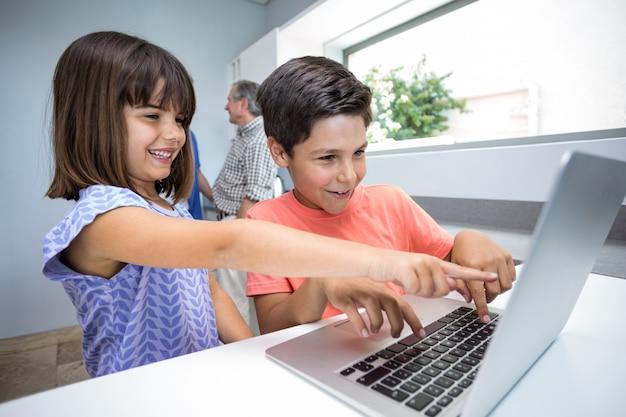 Szczęśliwa chłopiec i dziewczyna używa laptop Premium Zdjęcia