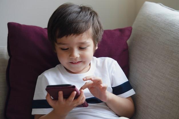 Szczęśliwa chłopiec ma zabawę bawić się grę na telefonie komórkowym Premium Zdjęcia