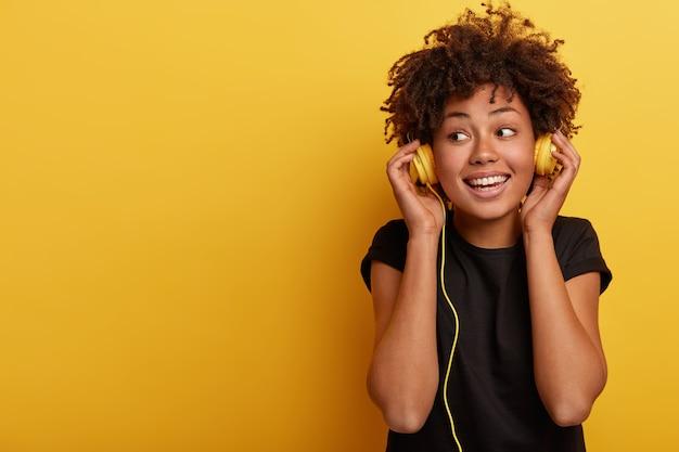 Szczęśliwa Ciemnoskóra Kobieta Nosi Przewodowe Słuchawki, Lubi Przyjemną Muzykę, Odwraca Wzrok, Ma Zębaty Uśmiech Darmowe Zdjęcia