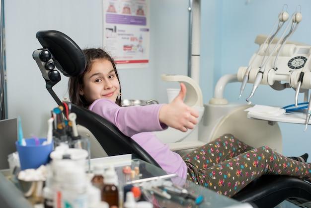 Szczęśliwa Cierpliwa Dziewczyna Pokazuje Aprobaty Przy Stomatologicznym Biurem. Koncepcja Medycyny, Stomatologii I Opieki Zdrowotnej Premium Zdjęcia