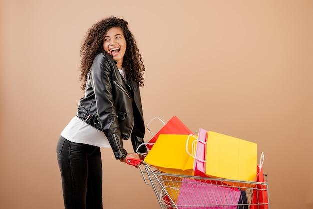 Szczęśliwa czarna dziewczyna z wózek na zakupy pełno kolorowe torby odizolowywać nad brązem Premium Zdjęcia