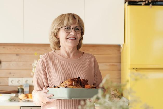 Szczęśliwa Dojrzała Kobieta Trzyma Danie Z Indykiem W Okularach I Uśmiecha Się Premium Zdjęcia