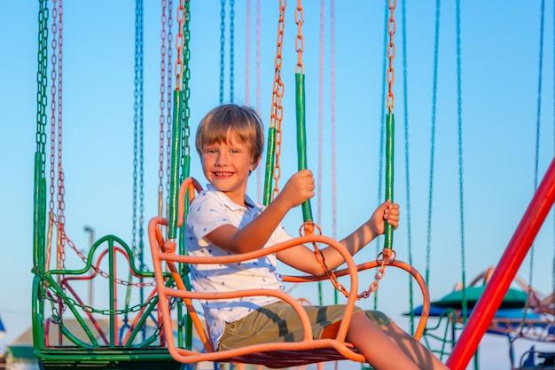 Szczęśliwa Dziecko Chłopiec Ma Zabawę W Parku Rozrywki. Przejażdżka Karuzelą łańcuchową. Premium Zdjęcia