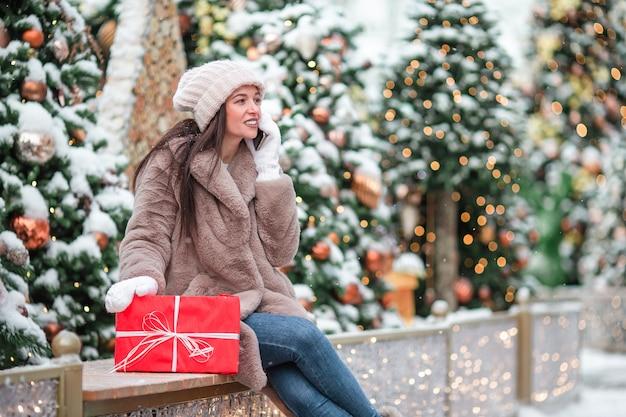 Szczęśliwa dziewczyna blisko jedliny gałąź w śniegu dla nowego roku. Premium Zdjęcia