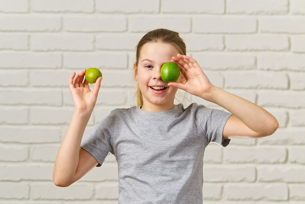 Szczęśliwa Dziewczyna Dobrze Się Bawi I Zasłaniając Oczy Wapnem, Zdrowe Odżywianie, żywność Ekologiczna, Dieta Owocowa, Koncepcja Premium Zdjęcia