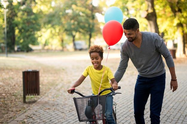 Szczęśliwa Dziewczyna Jedzie Na Rowerze, Podczas Gdy Ojciec Ją Uczy Darmowe Zdjęcia