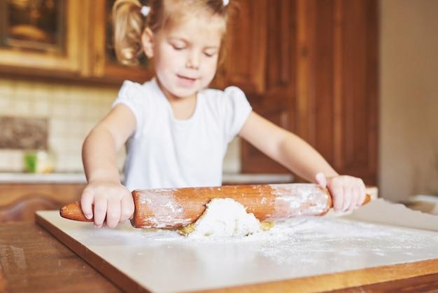 Szczęśliwa Dziewczyna Nosi Ciasto. Dziecko Zrobić Obiad W Garniturze Szefa Kuchni Darmowe Zdjęcia