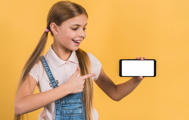 Szczęśliwa dziewczyna pokazuje coś na telefonie komórkowym z białym parawanowym pokazem Darmowe Zdjęcia