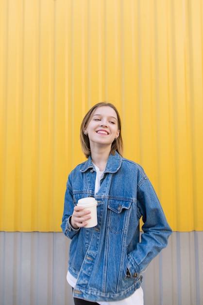 Szczęśliwa Dziewczyna Stoi Na żółtym Tle I Pije Kawę. Premium Zdjęcia
