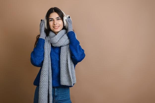 Szczęśliwa dziewczyna w futrzanych słuchawkach, ciepły i stylowy dodatek Premium Zdjęcia