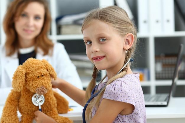 Szczęśliwa Dziewczyna Zabawy Z Misiem U Lekarza Premium Zdjęcia