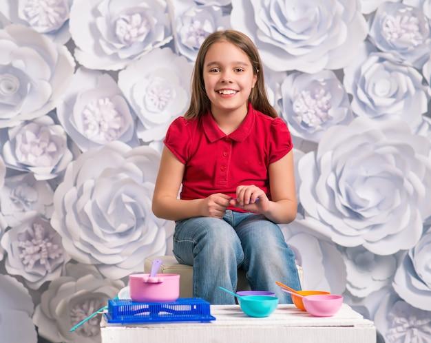 Szczęśliwa Dziewczynka Siedzi Przed Zabawkami Dla Dzieci Premium Zdjęcia