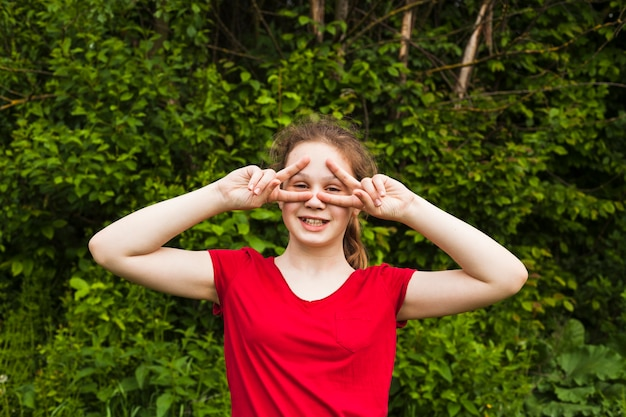 Szczęśliwa dziewczyny pozycja w parku i patrzeć przez znaka v Darmowe Zdjęcia