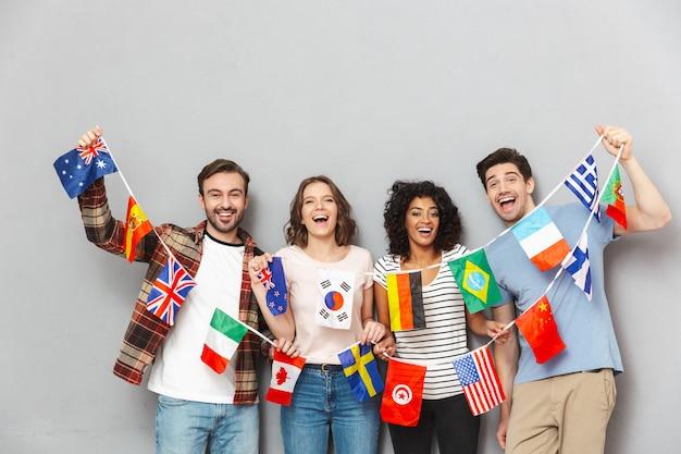 Szczęśliwa Grupa Przyjaciół Trzymająca Wiele Międzynarodowych Flag. Premium Zdjęcia