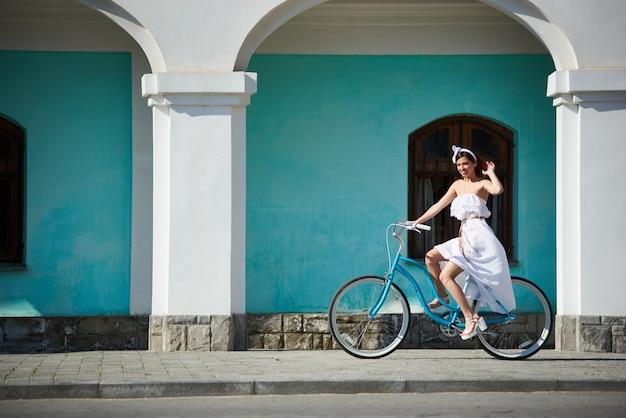 Szczęśliwa Kobieta Jedzie Na Rowerze Retro W Gorący Letni Dzień Na Ulicach Miasta Premium Zdjęcia