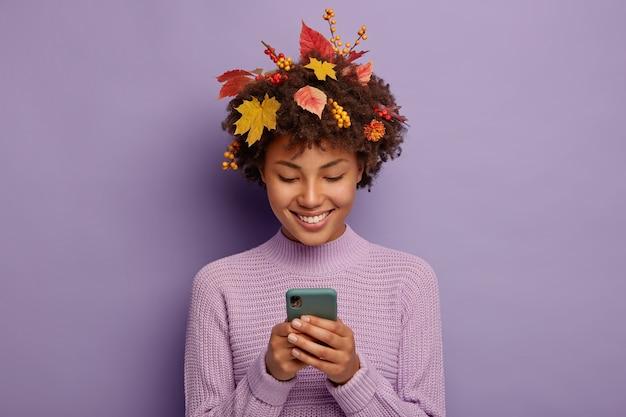 Szczęśliwa Kobieta Kręcona Rozmawia Z Przyjaciółmi Przez Komórkę, Ma Delikatny Uśmiech, Ma żółte Liście Na Głowie Darmowe Zdjęcia