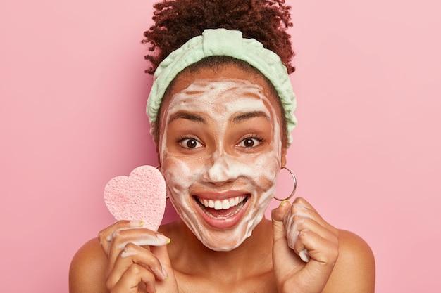 Szczęśliwa Kobieta Lubi Relaksować Się, Myje Twarz Bańką Mydlaną, Czuje Się Wypoczęta I Zachwycona, Trzyma Gąbkę Kosmetyczną Do Wycierania Cery Darmowe Zdjęcia