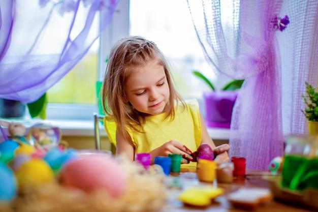 Szczęśliwa Kobieta Maluje Easter Jajka, Małe Dziecko W Domu Zabawę. Ferie Wiosenne Premium Zdjęcia