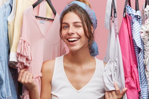 Szczęśliwa Kobieta Mrugając Oczami Stojąc W Pobliżu Regałów Z Ubraniami, Bawiąc Się I Pozytywnie Emocje Po Udanych Zakupach Darmowe Zdjęcia