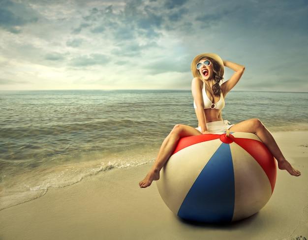 Szczęśliwa kobieta na ogromnej piłki plażowej Premium Zdjęcia