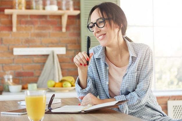 Szczęśliwa Kobieta O Atrakcyjnym Wyglądzie, Organizująca Przyjęcie, Spisuje Listę Zaproszonych Znajomych, Siada W Kuchni, Darmowe Zdjęcia