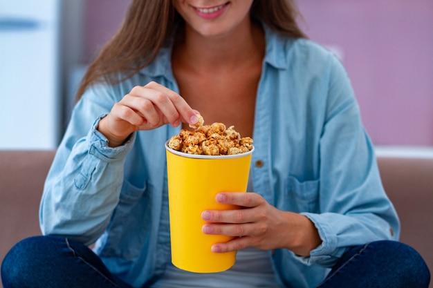 Szczęśliwa Kobieta Odpoczywa Chrupiącego Karmelu Popkorn I Je Podczas Gdy Oglądający Tv W Domu. Film Z Popcornem Premium Zdjęcia