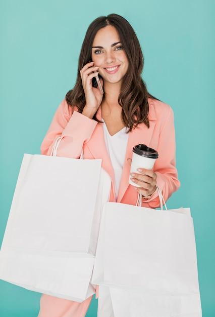 Szczęśliwa kobieta opowiada przy smartphone z kawą Darmowe Zdjęcia