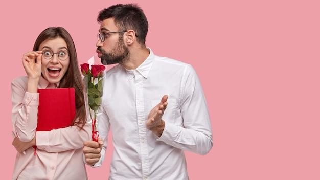 Szczęśliwa Kobieta Otrzymuje Czerwone Róże Od Przystojnego Faceta, Patrzy Pozytywnie Przez Okulary Darmowe Zdjęcia