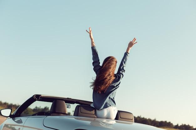 Szczęśliwa kobieta podróżnik w samochodzie cabrio Premium Zdjęcia