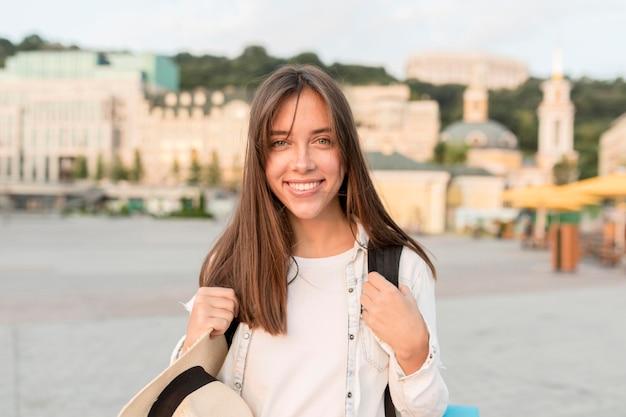 Szczęśliwa Kobieta Pozuje Na Zewnątrz Z Kapeluszem I Plecakiem Darmowe Zdjęcia