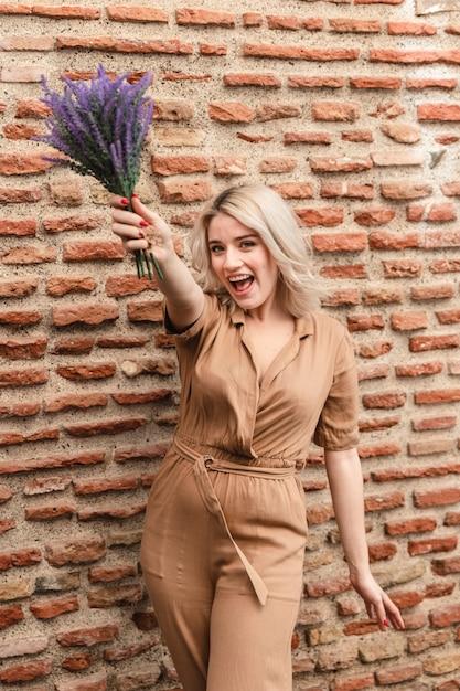 Szczęśliwa Kobieta Pozuje Podczas Gdy Trzymający Bukiet Lawendowi Kwiaty Darmowe Zdjęcia