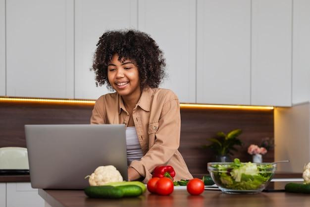 Szczęśliwa kobieta pracuje na laptopie w kuchni Darmowe Zdjęcia