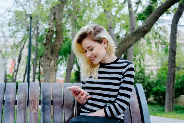 Szczęśliwa Kobieta Texting Na Smartphone Jest Ubranym Paskującego Wierzchołek I Siedzieć Plenerowy Na ławce Darmowe Zdjęcia