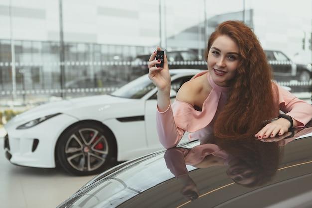 Szczęśliwa kobieta trzyma kluczyki do samochodu jej nowy samochód Premium Zdjęcia