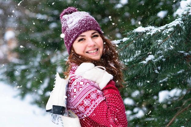Szczęśliwa Kobieta Trzyma łyżwy Zimowe Na Jej Ramieniu. Zajęcia Zimowe I Sport. Premium Zdjęcia