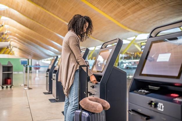 Szczęśliwa Kobieta Używa Odprawy Maszynę Na Lotnisku Dostaje Kartę Pokładową. Premium Zdjęcia