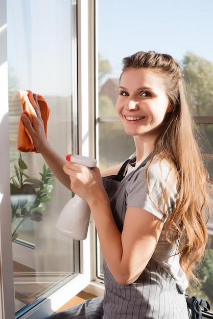 Szczęśliwa Kobieta W Rękawice Czyszczenia Okna Z Szmatką I Sprayem Do Mycia W Domu Premium Zdjęcia