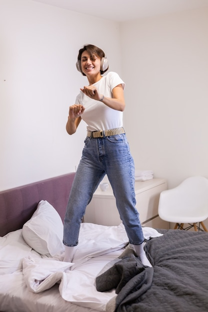 Szczęśliwa Kobieta W Ubranie W Domu W Sypialni Słucha Muzyki W Słuchawkach, Tańczy I Skacze Darmowe Zdjęcia