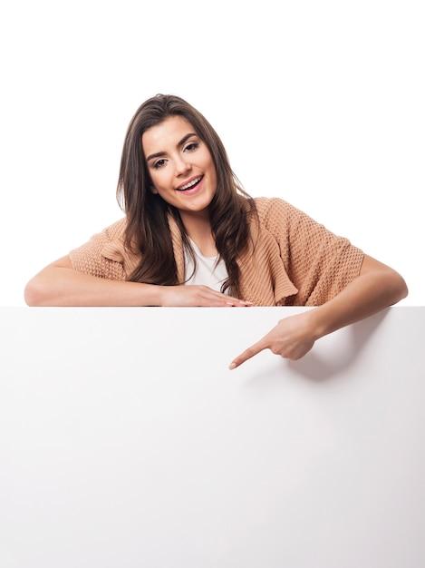 Szczęśliwa Kobieta, Wskazując Na Pustą Tablicę Darmowe Zdjęcia