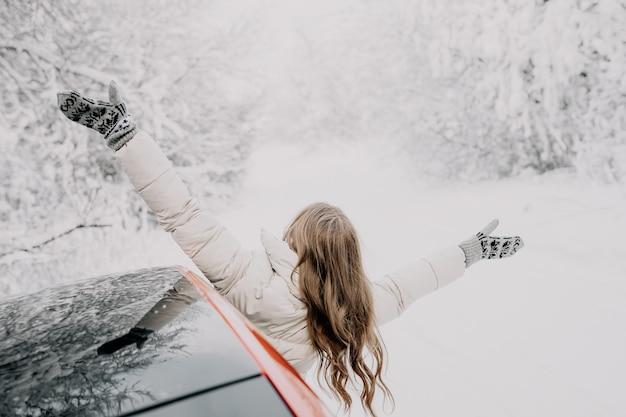 Szczęśliwa Kobieta Wygląda Przez Okno Samochodu, Rozkładając Ramiona W Różnych Kierunkach. Zimowy Las. Premium Zdjęcia