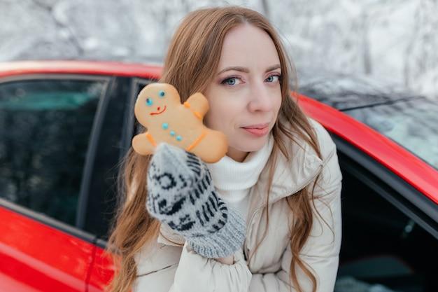 Szczęśliwa Kobieta Wygląda Przez Okno Samochodu, Trzyma W Rękach Ciasteczko W Postaci Mężczyzny. Na Tle Zimowego Lasu. Premium Zdjęcia