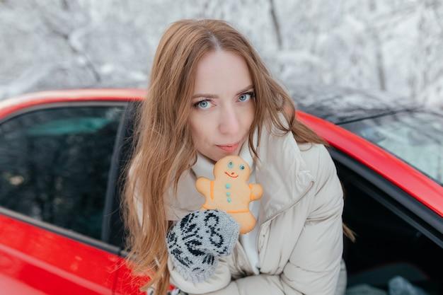 Szczęśliwa Kobieta Wygląda Przez Okno Samochodu, Trzyma W Rękach Ciasteczko W Postaci Mężczyzny. Zimowy Las. Premium Zdjęcia